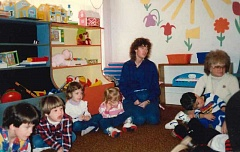 CONTRIBUTED PHOTO - Sue Phillips (blue shirt) sits with a crowd of children while assisting in the classroom at Larsen Learning Center several years ago.