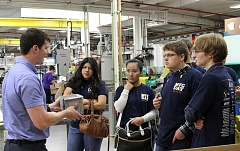 SUBMITTED PHOTO - Students from Aloha High School, here sporting their Manufacturing Day T-shirts, learned about plastics manufacturing from Grant Bacon (left) and helped create their own whistles at Elite Plastics in Beaverton on Friday.