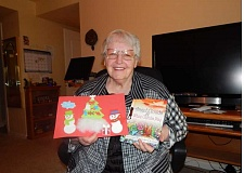 BARBARA SHERMAN - PJ Cowan holds her last and only adult book, 'Angel Clouds & Where Cherubs Play,' along with a decorated thank-you card from a young child who received one of her children's books.