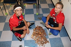 SUBMITTED PHOTO -  Gardiner sixth-graders CamRon McDonald (left) and Grey Hanks get on the floor to count pennies for UNICEF.