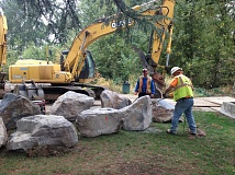 PHOTO BY TONIA BURNS - Workers drill holes in huge boulders to enable them to be attached to logs, which will then be placed in the river, slowing waterflow so migrating fish can rest.