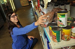 STAFF PHOTO: VERN UYETAKE - Volunteer Eve Goldshere of Lake Oswego works on stocking the shelves.
