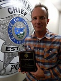 REVIEW PHOTO: CLIFF NEWELL - LOPD Detective Jonithan Funkhouser shows his Distinguished Service Award from the Oregon Peace Officers Association.