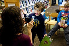 TIMES PHOTO: JAIME VALDEZ - Michael Cohn,7, gives his book review of 'The Lost Boy,' a true story true story of Dave Pelzer, while being recorded by his mom, Lisa, at the Beaverton Library.