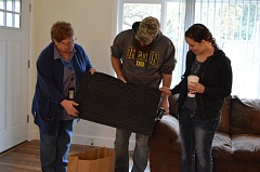 SPOTLIGHT PHOTO: NICOLE THILL - Sally McLaughlin, homeowner specialist at Community Action Team, hands Jason and Jessica Smith,  a St. Helens couple, a welcome mat as a housewarming gift. The Smith family was able to renovate a foreclosed home in St. Helens with the help of the home acquisition program.