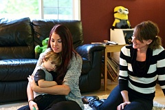 TIMES PHOTO: JAIME VALDEZ - Jessi Thorne holds her son, Landon Nash, 2, as her mom, Tina Brewster, watches on at their home in Tualatin.