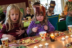 TIMES PHOTO: JONATHAN HOUSE - Stafford Country Montessori students Paige Granum, left, and Charlotte Hamilton-Kerr enjoy a Thanksgiving feast.