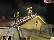 SUBMITTED PHOTO - Firefighters try to douse a fire in the attic and other spots at the Bazaar Market on Southwest Canyon Road.