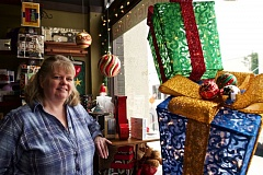 TIMES PHOTO: JAIME VALDEZ - Deb Messina, owner of Quilters Corner Store, stands by window of her store thats decorated for the Small Boxes Beaverton shopping event that starts this Saturday after Thanksgiving. Messina organized the event for the Beaverton Downtown Association.verton Downtown Association.