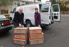 PAMPLIN MEDIA GROUP: BARBARA SHERMAN - Jay Gilbertson, director of the Tigard Senior Center, gets ready to load up six boxes of coats destined for the Bethlehem House of Bread with volunteer Marisa Walloch.