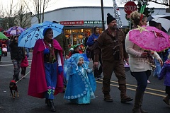 COURTESY PHOTO - Participants in last year's Umbrella Parade march on Milwaukie's Main Street, in colorful holiday attire. This year, 30 lucky children will join Santa as he rides the  Max Orange Line across Tilikum Crossing and back.