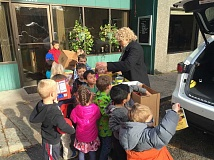 SUBMITTED PHOTO - Students in Madeline Bisenius' class help load food into a car for Union Gospel Mission in Portland. Students at Bisenius' school, Touchstone Preschool in Tigard, raised enough food to feed a dozen people for Thanksgiving.