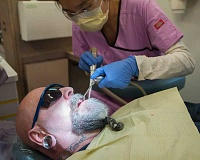 OUTLOOK PHOTO: JOSH KULLA - Jeffrey Bernard, an unemployed 59-year-old Portland resident, has a tooth extracted Tuesday at a free dental clinic run by Medical Teams International volunteers, including a retired dentist shown here, who asked to remain anonymous.