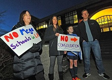 REVIEW PHOTO: VERN UYETAKE - Community members gathered before a school board meeting Monday to express their disapproval of a vision for one high school in Lake Oswego. From left: Krissy Wygarden; and Maya, Rachel and David Barba.