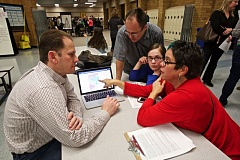 TIMES PHOTO: JAIME VALDEZ - Darren Hart, left, listens as Susan Finch shares her concerns about what draft high school boundary changes would mean to friends as Brad Larson and his daughter, Sarah, 13, listen during a high school boundary open house in the commons of Five Oaks Middle School. Hart and Larson created software that helps residents experiment with high school attendance boundary changes.
