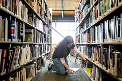 TIMES PHOTO: JONATHAN HOUSE - A volunteer shelves books at the Tigard Public Library in January.