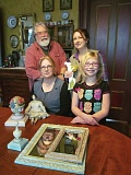PHOTO BY ELLEN SPITALERI - Members of the LeFever family display their wares, including painted finials and Annabeth, the doll. Back row, Gregory LeFever and Brigitte LeFever, holding one of her chalkware rabbits. Front row, Christine LeFever and Gracie, Brigitte's daughter.