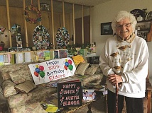 LINDSAY KEEFER - Eldora Lowry, who lives on her own in Woodburn Estates, shows off the cards and gifts she received for her 100th birthday, which was March 8. A photo on the coffee table in the center is from her own mother's 100th birthday decades ago. Lowry's mother lived to be 102.