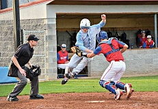 COURTESY PHOTO: MICHELLE NOLASCO - Liberty senior Renner Stecki jumps to try to elude the tag of Hilhi catcher Garrett Lusey on a play at the plate during Tuesday's NWOC baseball game at Hare Field. Liberty held off a late Hilhi rally to win the game by a 5-4 score.