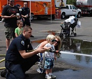 COURTESY OF TVF&R - Tualatin Valley Fire & Rescue Volunteer Firefighter Teddy Wollam helps a young visitor spray a fire hose during last years Sherwood Community Services Fair at Station 33.