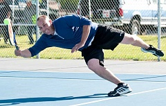 LON AUSTIN/CENTRAL OREGONIAN - Crook County High School boys tennis coach Jonny Oelkers reaches for a ball during the team's Blue and Gold doubles tournament and fundraiser on Saturday. Oelkers and his partner, Dave Schultz, finished third in the advanced division of the tournament.