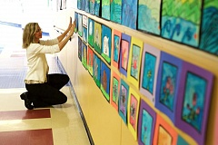 TIMES PHOTO: JAIME VALDEZ - Second-grade teacher Carol Poland hangs art in the hallway at Beavers Acres Elementary School to be featured for the schools fundraiser ARTS4smARTS.