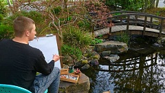 ANN BRUCKER - Nathan Brucker holds a bamboo brush while observing the Arts Loft's scenic garden.