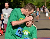 STAFF PHOTOS: VERN UYETAKE - Jon Stucky of Lake Oswego gives his son Jacob a kiss on the head after the two completed the 5k race together.