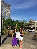 STAFF PHOTOS: VERN UYETAKE  - Shannen Knight, left, who has been involved with West Linns farmers market for the last three years, poses with Erika Vincent with a poster advertising Wednesdays in Willamette.