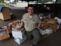 SUBMITTED PHOTOS - Camden Fobert stands proudly with the more than 3,500 books he helped collect for the Clackamas Bookshelf.