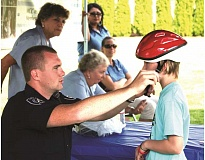 MPD - A Molalla Police officer fits a new bicycle helmet. Molalla Communications Company is again providing free helmets at this year's event.