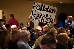 PHOTOS BY ADAM WICKHAM - Albert Zayha of the South Portland Air Quality Neighborhood Group holds a sign at the Monarch Hotel.