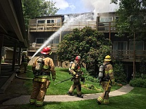 SUBMITTED PHOTO - Firefighters direct water into a unit at the Tanglewood Hills Condos in Lake Oswego on Wednesday. It took crews about 30 minutes to extinguish the blaze.