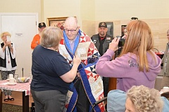 Representing the Quilts of Valor Foundation, Faith Holloway on April 30 presents a quilt to Verland Huff, who served in the Navy during WWII.