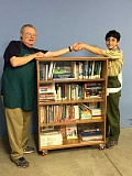 SUBMITTED PHOTO: ELIZABETH LINSER - Kekoa Linser Lemke stands by his completed project and shakes hands with Mike Shiffer, board president of Tualatin School House Pantry.
