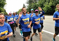REVIEW PHOTO: VERN UYETAKE - Officers Dawn Pecoraro and Rusty Palmari of the Lake Oswego Police Department wave as they head out on Friday morning's Law Enforcement Torch Run. The 30th-annual event was a benefit for Special Olympics Oregon.