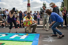 OUTLOOK PHOTO: JOSH KULLA - Engineer Austin Bennington (yellow vest) measures a 14,400-piece wooden mosaic Saturday to ensure an official Guiness Book world record for the largest such piece of art ever assembled. At right are official world record witnesses Laurel Porter of KGW News (front right) and Gresham Chamber President Lynn Snodgrass (directly behind Porter). The record took place at the Gresham Arts Festival.