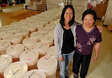 TRIBUNE PHOTO: VERN UYETAKE - Michelle Ly (left), and her mother Kim Trinh came to Wilsonville as refugees witih their family in 1979. Their family has brewed baijiu for generations.