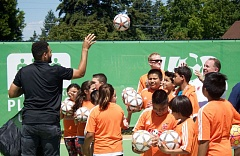 OUTLOOK PHOTO - Andre Akpan with the U.S. Soccer Foundation tosses soccer balls out to the kids for the innagural game.