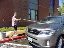 GAZETTE PHOTO: RAY PITZ - Sherwood City Manager Joe Gall washes the Kia of Chris Hannan in an effort to raise money for th Sherwood Relay for Life, a fundraiser for the American Cancer Society set for Aug. 6 at Sherwood High School.