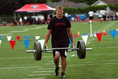 DAN BROOD - Tualatin High School senior-to-be Josh Chandler competes in the farmer's carry event at the Metro Area Lineman Challenge. Chandler set a new record in the bench press.
