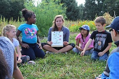 PMG PHOTO: NICOLE THILL - Kate Nootenboom, an intern at the Sauvie Island Center, talks to a group of campers about the various parts of a plant's structure. Learning about the physical aspects of a plant is just one area of education students learn about during the five-day camp.