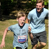 SETH GORDON - With encouragement from Veritas Running Camp counselor Thomas Lattus, John Paul Lattus legs out the last few meters of the 3K middle school race Friday morning at Jaquith Park. In its first year, head coach Ken McChesney's camp drew 28 youth runners.