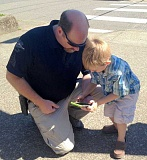 TIDINGS PHOTOS: PATRICK MALEE - West Linn Police Sergeant Mike Francis and Benjamin Lewis, 4, scan the area for Pokemon.