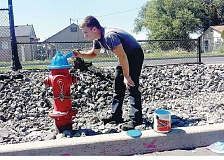 SUBMITTED PHOTO - Logan Lachenmeier, a fire student with the Jefferson County Fire Department, paints the bonnet of a fire hydrant blue, to signify that it has enough water pressure to put out more than 1,500 gallons per minute.