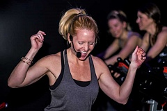 SUBMITTED PHOTO - Andrea Fenton leads workouts by blacklight at Ride PDX in the South Waterfront neighborhood.