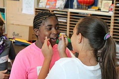 TIDINGS PHOTO: ANDREW KILSTROM - Sixth-grader Alexis Corso gets ready to draw cat whiskers on classmate Alyssa Samuel during Survivor Day Aug. 30.