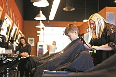 JAIME VALDEZ - Elliott Hunter, 5, gets a haircut from Kristi Brush, a barber from The Barbers at Progress Ridge TownSquare.