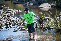 TRIBUNE PHOTO: DIEGO DIAZ - A volunteer finds plenty of trash in and around the water during the annual Johnson Creek Clean Up. DEQ has vowed to check whether a former dump is leaking industrial waste into the creek.