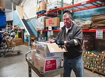 OUTLOOK PHOTO - SnowCap volunteer and past board president Jim Liefeld works in SnowCaps warehouse, stocking shelves with canned food donations.